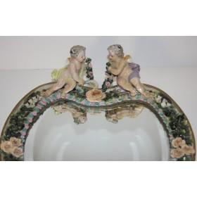 Антикварное зеркало в фарфоровой оправе с купидонами